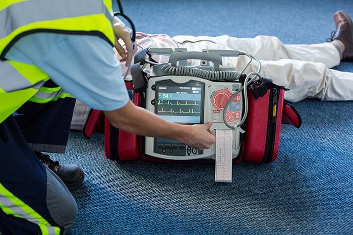 Paramedic using an external defibrillator