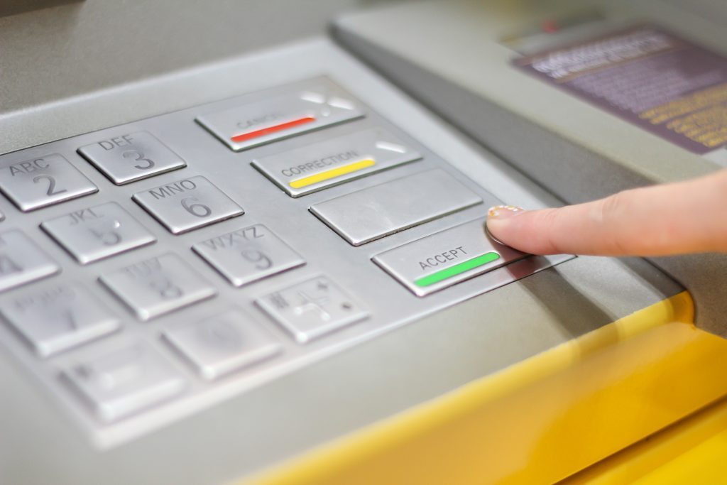 Someone interacting with an ATM keypad showing the raised areas of keys.
