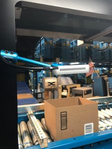 Intel RealSense depth camera scanning the contents of a box on a conveyor belt
