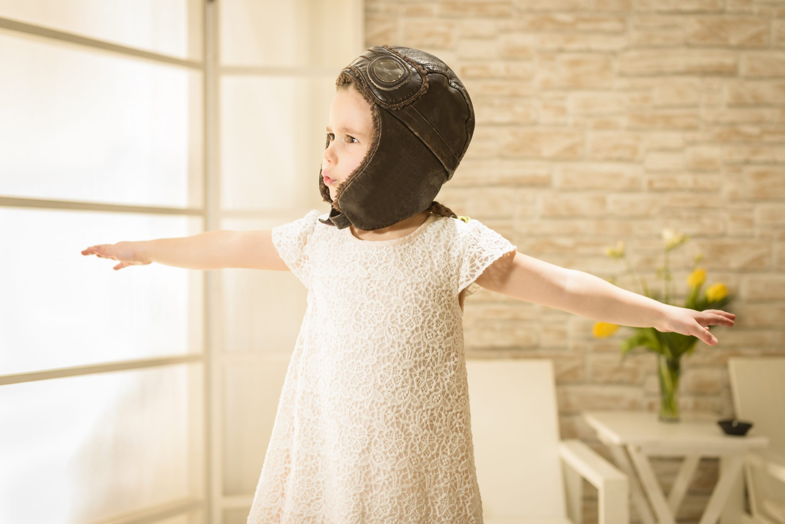 Small girl pretending to be a plane or a bird